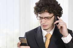 Troubled business man with two mobile phone Royalty Free Stock Photos