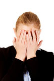 Troubled business woman covering her face with hands Stock Image