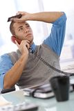 Troubled businessman on call. Troubled businessman at desk concentrating on landline phone call, holding mobile phone, looking up royalty free stock photography