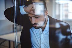 Troubled businessman leaning on a glass wall. And closing his eyes Stock Photography