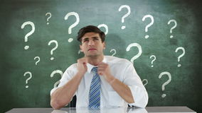 Troubled businessman looking up. Against question marks stock footage
