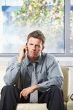 Troubled businessman on phonecall. Troubled businessman focusing on phonecall sitting on leather couch thinking Stock Photo