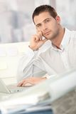 Troubled businessman sitting at desk. In office Stock Image