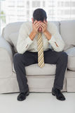 Troubled businessman sitting on sofa Stock Images