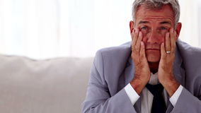 Troubled businessman sitting on a sofa. And holding his head between hands stock footage