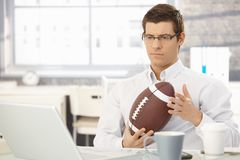 Troubled businessman thinking holding football. Troubled businessman thinking about work playing with football handheld in office Stock Photography