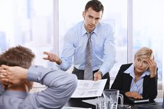 Troubled businesspeople at meeting. Troubled businesspeople discussing report at meeting, businessman showing document to boss with asking gesture Royalty Free Stock Image