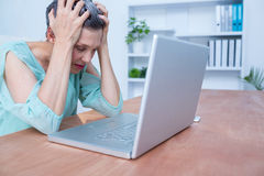 Troubled businesswoman frowning on her laptop Royalty Free Stock Photography