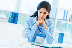 Troubled businesswoman. Image of a troubled businesswoman reviewing financial statistics Stock Image