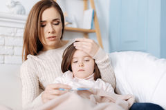 Troubled caring mother curing her daughter Royalty Free Stock Photos