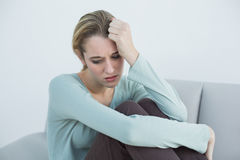 Troubled casual woman sitting on couch. In the living room stock photo