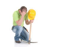 Troubled construction worker. Handsome young troubled construction worker with pickax, mattock, pensive look,  studio shot,  white background Stock Images