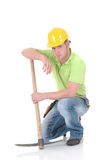 Troubled construction worker. Handsome young troubled construction worker with pickax, mattock, pensive look,  studio shot,  white background Stock Photography