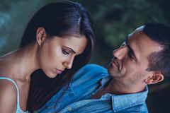 Troubled couple hugging and looking down Stock Images
