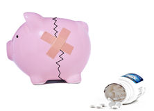 Troubled finances. Financial crises concept made of a piggy bank and an white pills Stock Images