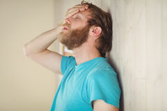 Troubled hipster leaning against wall Stock Photography