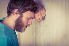 Troubled hipster leaning against wall Stock Photos