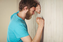 Troubled hipster leaning against wall Royalty Free Stock Photo