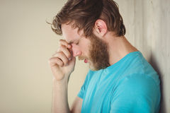 Troubled hipster leaning against wall Stock Image