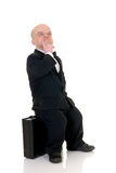 Troubled little businessman. Dwarf in a formal suit with bow tie next to  suitcase, studio shot, white background Royalty Free Stock Images