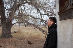 Troubled and lonely teenager. Troubled teen at an abandoned house with a barren tree in the background royalty free stock photo