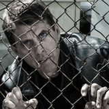 Troubled Man. Desperate looking man gripping a wire fence stock image