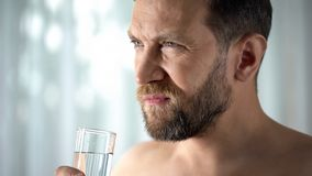 Troubled man drinking water from cup, taking pills, feeling ache, painkillers. Stock photo stock photo