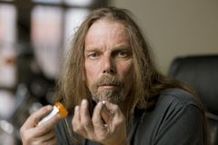 Man with an Opioid Pill. Troubled man holding a prescription opioid pill and bottle royalty free stock images