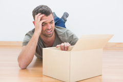 Troubled man open a moving box at home Stock Photos