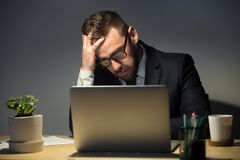 Troubled man reading about recent problem late at night. Too much work concept. Troubled man in glasses reading about recent problem on laptop computer, deep in stock photos