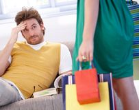 Troubled man and shopaholic woman. Young man looking troubled when shopaholic woman arriving home with shopping bags Stock Image