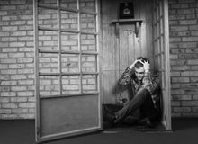 Troubled Man Sitting on Floor of Telephone Booth Stock Images