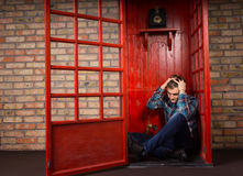 Troubled Man Sitting on Floor of Telephone Booth. Troubled Man Sitting on Floor in Corner of Public Telephone Booth and Holding Head in Hands stock photography
