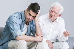 Troubled man talking with father. Troubled young men talking with elder father Royalty Free Stock Photography