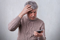 A troubled mature man holding his hand on his gray head while using smartphone reading some news in the Internet. A man having sho Stock Photo