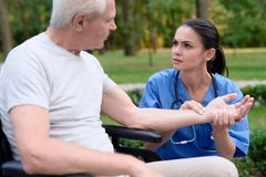 A troubled nurse measures the pulse of an old man who is sitting in a wheelchair. Care for the older generation. A worried nurse measures the pulse of an old men Stock Image