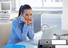 Troubled office girl looking at laptop screen. Troubled office worker girl sitting at desk, looking at laptop computer screen, worried Stock Image