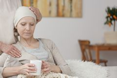 Troubled patient with tumor. Troubled patient with cancer tumor holding a cup of tea while being comforted by a family member Stock Photos