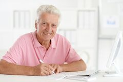 Troubled senior man. Using computer in office stock photography