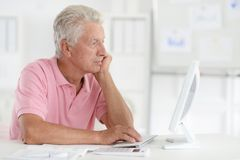 Close up portrait of troubled senior man. Troubled senior man using computer in office royalty free stock photos