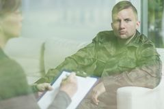 Troubled soldier during psychotherapy session. At psychiatrist's office Royalty Free Stock Photos