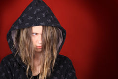 Troubled teen. Ager with hooded sweater on a red background Stock Images