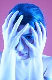 Troubled Teen 2. Portrait of a troubled woman covering her face with her hands.  One eye is visible between her fingers.  Blue tint.  Isolated on pink background Royalty Free Stock Photography
