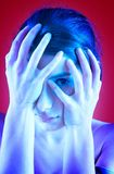 Troubled Teenager. Portrait of a troubled teenager covering her face with her hands. One eye is visible between her fingers. Blue tint. Isolated on red royalty free stock photography