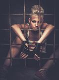 Troubled teenager in cell. Troubled teenager girl behind bars stock image