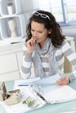 Troubled woman calculating budget. At home, money, bills and finances Stock Image
