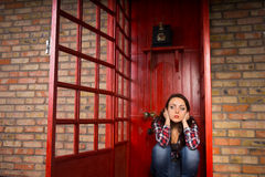 Troubled Woman Crouching in Red Telephone Booth Stock Images
