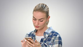 Troubled woman reading bad text news on phone touching her head in misery on white background. Troubled woman reading bad text news on phone touching her head stock video footage