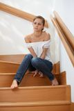 Troubled woman at staircase. Troubled woman sitting at staircase at home, looking away Stock Image