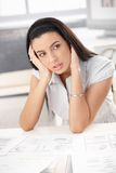 Troubled woman thinking. Troubled woman sitting at desk with business documents, thinking royalty free stock image